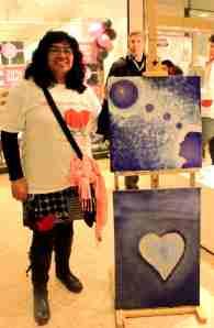 Lupita med två av sina målningar